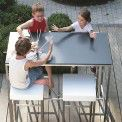La table haute ROLBLOC, plateau en HPL TRESPA, structure et piétement en inox, par JOLI, convient pour un usage en intérieur ou extérieur